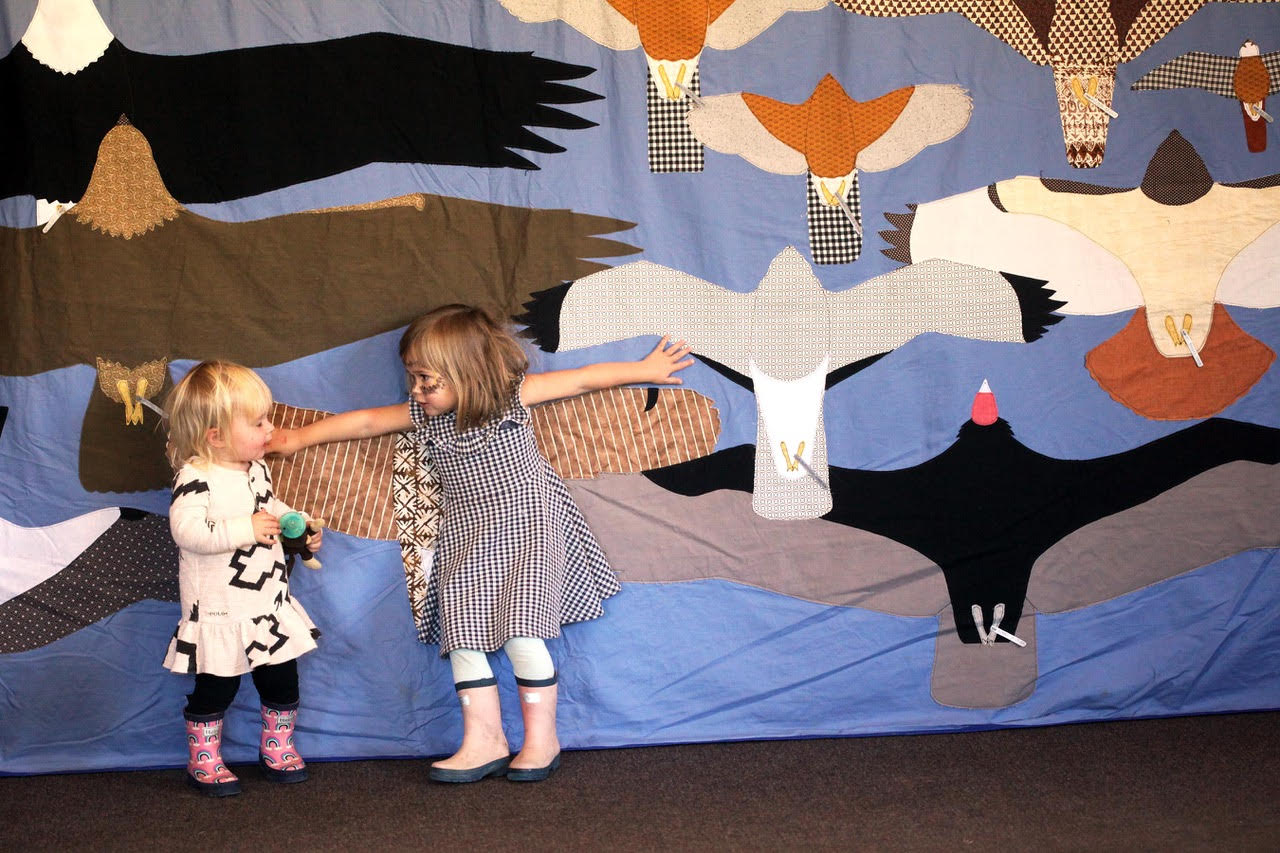 two children compare their wingspans to those of birds on a quilt behind them