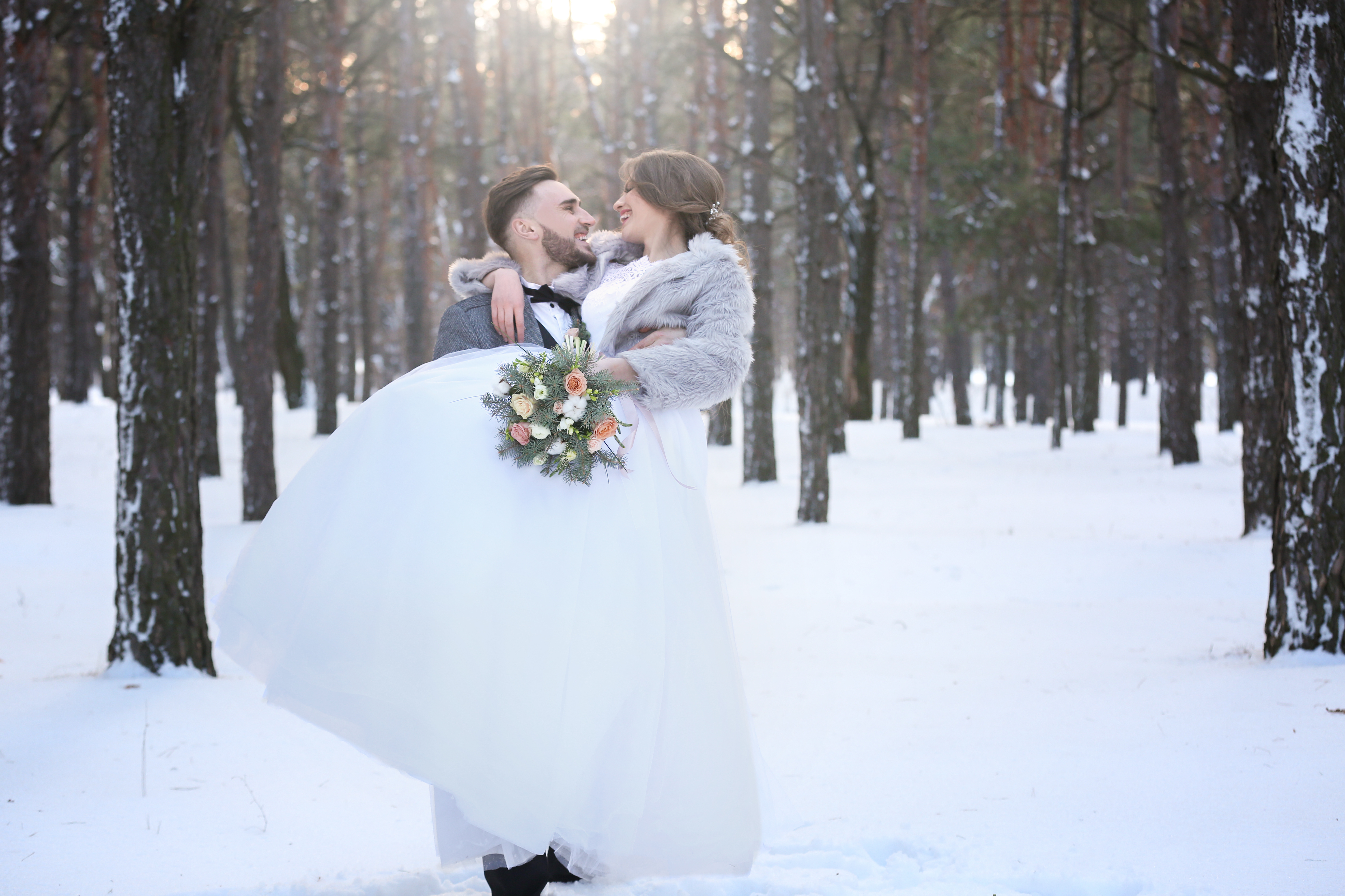 couple embracing in the snow at their winter wedding