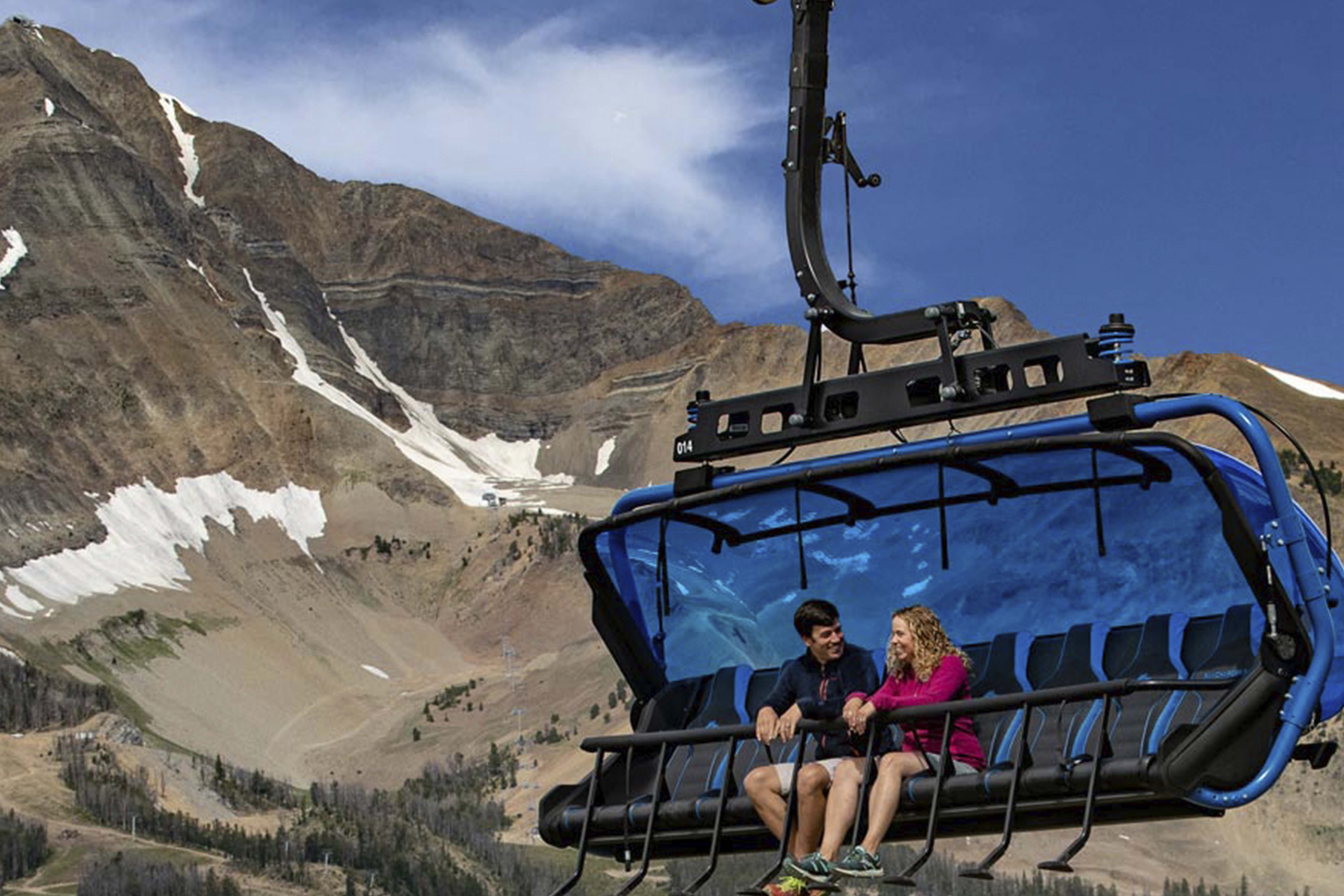 two people on the loan peak sky lift at big sky in the summer