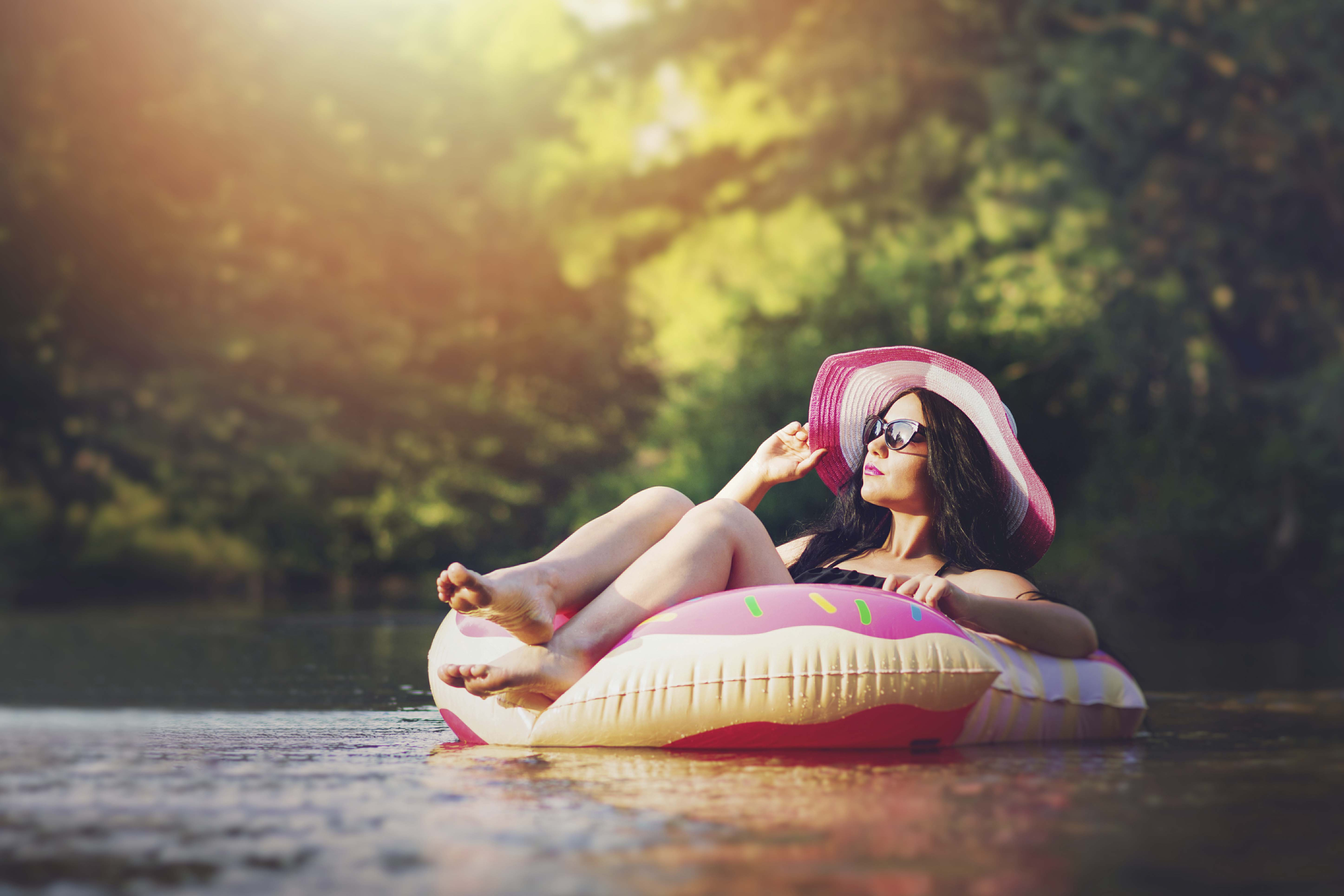 woman floating on a river while wearing a sun hat